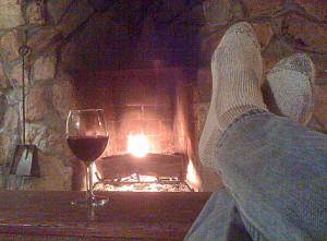 Image of feet up in front of a cozy fireplace