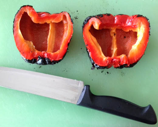 Cut red bell peppers in half after steaming